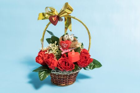 Basket with a bouquet of colorful roses isolated over white