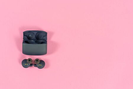 Wireless headphones on pink table with background