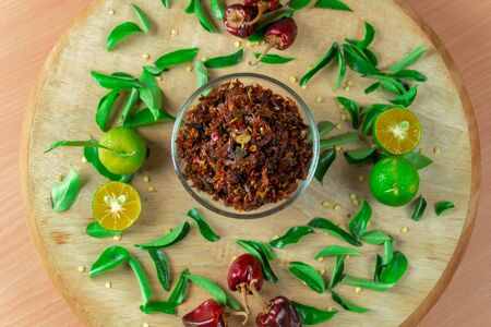 Spicy Chili paste with peppers and lime on wood bacground