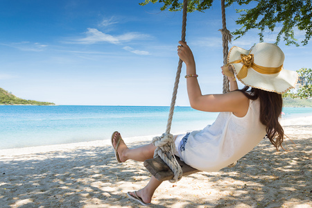 fun activity: Girl on swing at the beach in Thailand Stock Photo