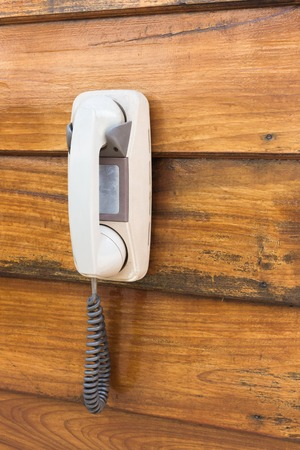 White older analog phones hanging on wooden wall.