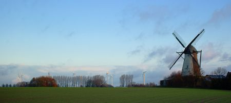 traditional windmill: Morning light, traditional windmill in the foreground and modern windmill generators on a background Stock Photo