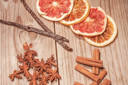 anis: Dry fruits, vanilla- and cinnamon sticks and star anis. On wooden background Stock Photo