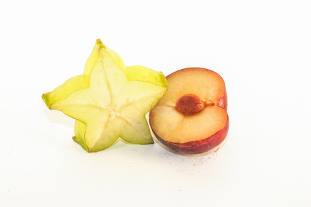 Green carambola and purple plum, on white background photo