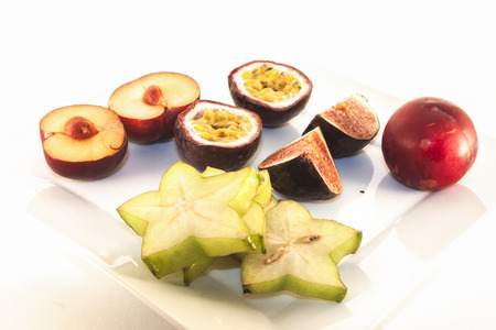 purple fig: Green carambola, purple fig,colorful passion fruit and lilac plum, on white background