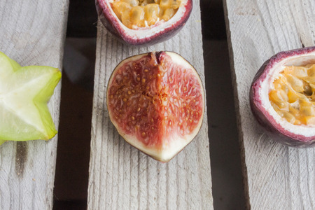 purple fig: Purple fig, near carambola, passion fruit and plum, on wooden background Stock Photo