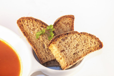 ide: Bread and parsley, on the ide of a soup bowl