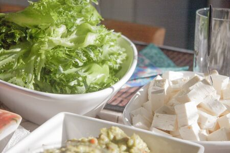 Green sallad and feta cheese, at a table Stock Photo