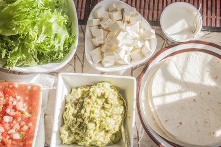 tex: Delicious tex mex tortilla table. including tortillas,salsa, guacamole, feta cheese and salad