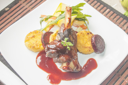 lamb shank: A plate full of lamb shank, red wine sauce, polenta, beetroot and salad