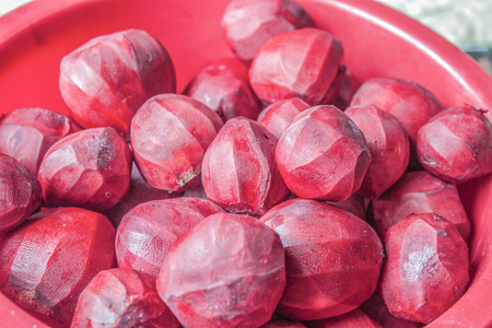 red skinned: Skinned, raw, purple beetroots, in a red plastic bowl.