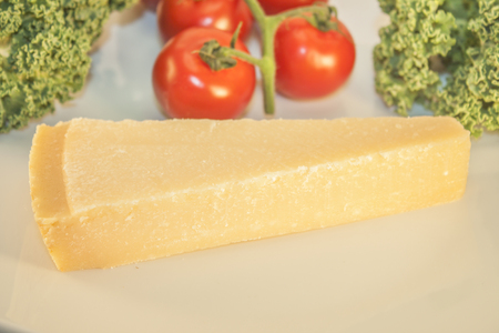 wedge: A parmesan wedge, in front of tomatoes and kale