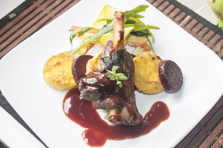 wine sauce: A plate full of lamb shank, red wine sauce, polenta, beetroot and salad