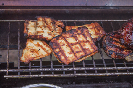 haloumi: Slices of grilled halloumi, near meat, on a barbeque Stock Photo