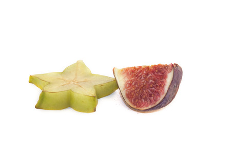 purple fig: A green carambola and a purple fig, on white background