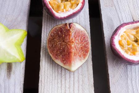 grenadilla: Purple fig, near carambola, passion fruit and plum, on wooden background Stock Photo