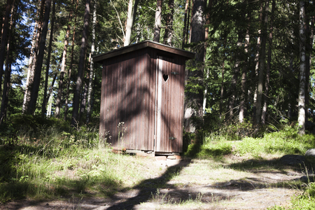 outhouse: A lonely, brown outhouse, in the forrest Stock Photo