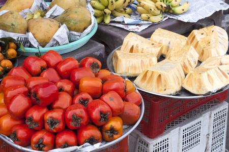 diospyros: Red persimon fruits, Diospyros kaki, near mango, orange, durian and banana