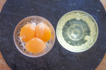 yolks: Egg yolks and whites, on a stone plate