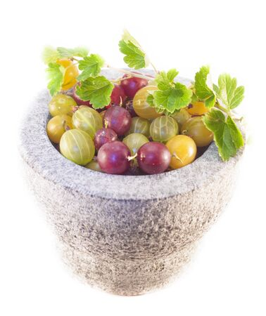 ribes: Yellow, red and green gooseberries, ribes uva-crispa in a stone bowl, isolated on white background Stock Photo