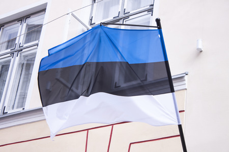 estonian: A flagpole with a estonian flag, at a house wall