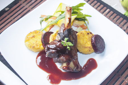 shank: A plate full of lamb shank, red wine sauce, polenta, beetroot and salad