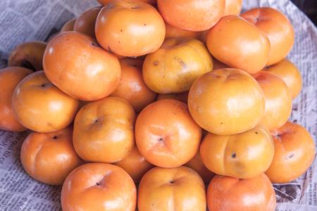 diospyros: A lot of orage Diospyros kaki, persimmons, at a market in Phu Quoc, Vietnam
