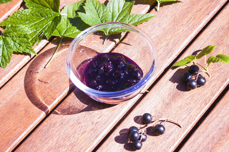 glass bowl: A glass bowl full of tasty black currant jam, in between black currant leaves and berry ripes Stock Photo