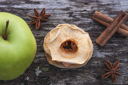 anis: A pile of dehydrated dry apples, between a green apple, star anis and cinnamon sticks, at a forrest