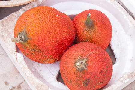 dicotyledon: A few red gourd or gac fruits, at a market