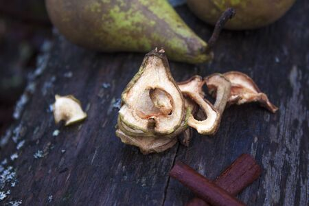 pyrus: Dried pears, pyrus communis, near wet cinnamon sticks and fresh green pears