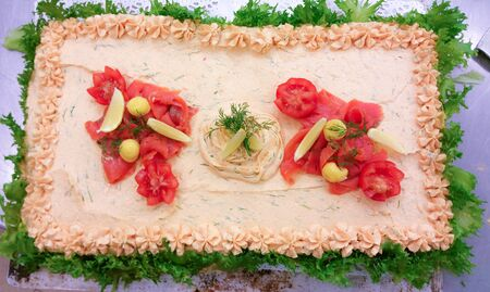 Salmon sandwich cake, decorated with sallad,lemon creme, dill and coldsmoked salmon