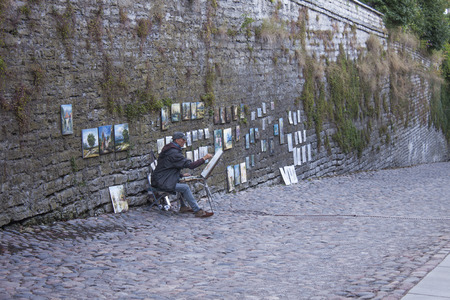 tallin: TALLIN, ESTONIA – JULY 5TH, 2015: Artist drawing and selling paintings, on the street to old town tallin