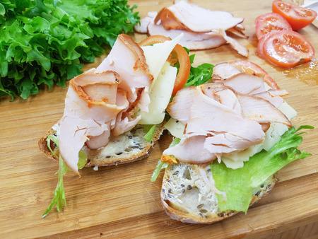 Two turkey bread sandwishes, on a wooden cutting board