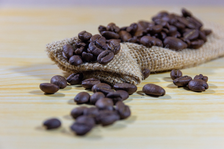 Selective focus coffee beans and grinded beans in vintage wooden coffee grinder and sackcloth on wooden background 免版税图像