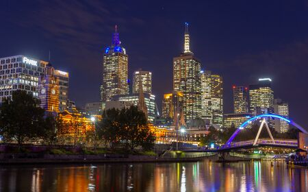 Yarra River and  Melbourne city at night looking towards Flinders Street Station . Australia