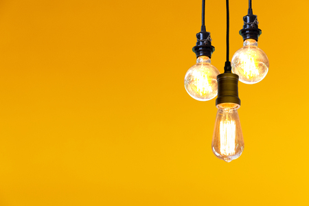 Vintage light bulb hanging over yellow background, Idea concept.