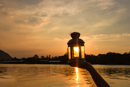 lamp on hand in sunbeam over sunset. power and idea concept