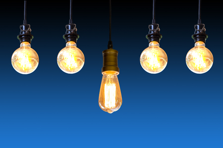 Vintage light bulb hanging over dark blue background, Idea concept.