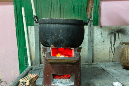 Cooking aluminum pot boiling on charcoal burning stove. Stock Photo
