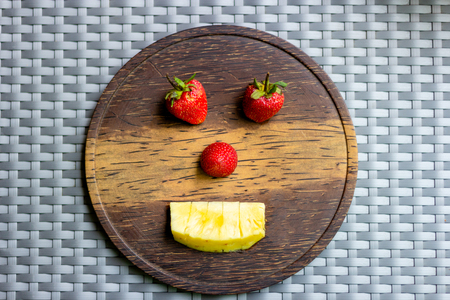 Strawberry and pineapple on wooden plate create shape a robot