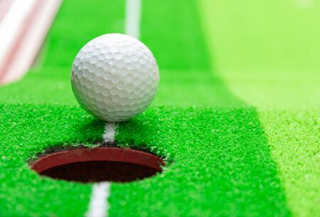 golf ball on lip of cup, goal concept 스톡 콘텐츠