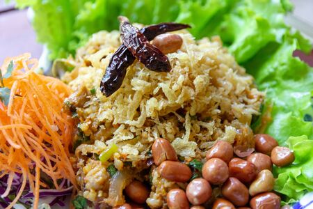 Yam Naem Khao Thot is Spicy Salad of Curried Rice Croquettes, Fermented Pork, Ginger and Peanuts on plate.Thai food