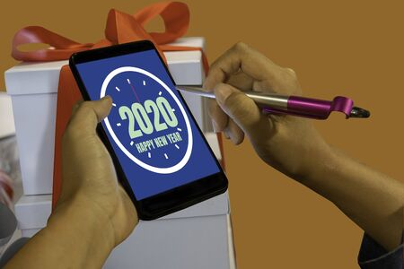 2020 New Year on mobile phone with gift box on golden brown background. 스톡 콘텐츠