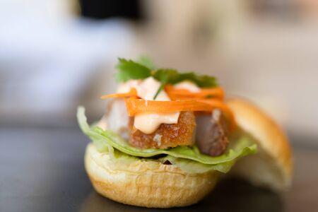 fresh crispy pork burger on wood table Standard-Bild