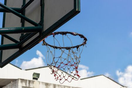 Close up basketball hoop and basket with white sky on background in the public arena