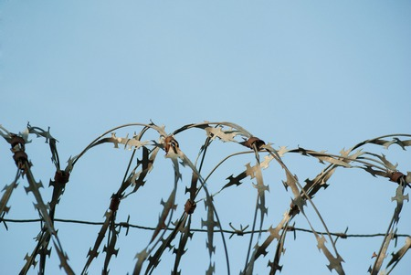 Barbed wire fencing against the blue sky Imagens
