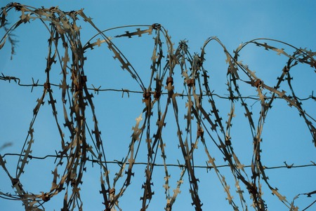 Old rusty barbed wire fencing against the blue sky