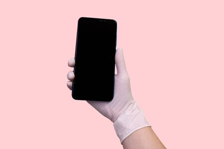hand in a medical glove holds a smartphone