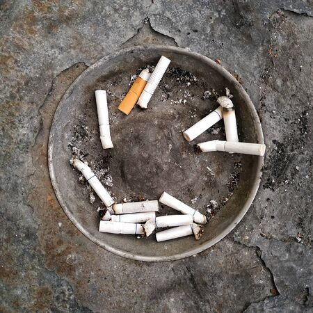 cigarette butts in a street ashtray
